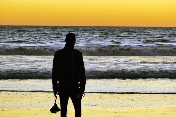 photo l'homme devant la mer